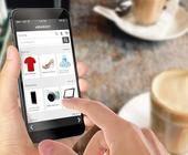 Online-Shopping mit Smartphone. Schreibtisch mit Kaffee im Hintergrund.